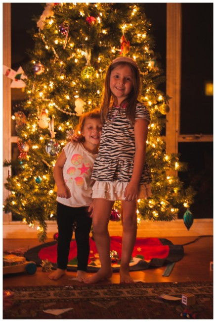 sisters hugging in front of a christmas tree