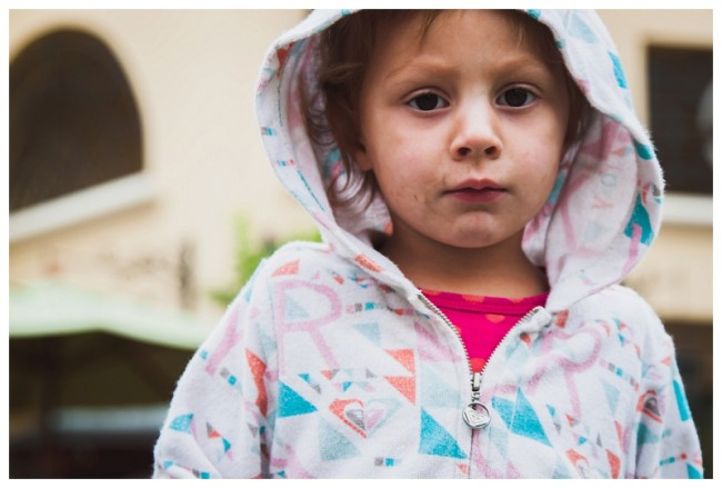 little girl in a hoodie looking at camera