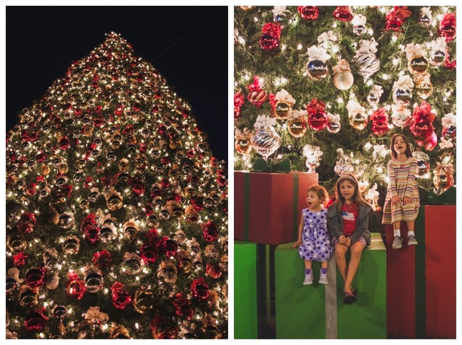 3 sisters sitting in front of a christmas tree