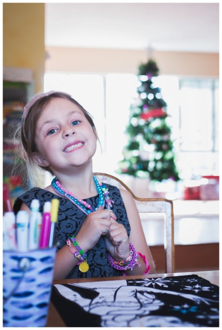 little girl drawing in front of a christmas tree