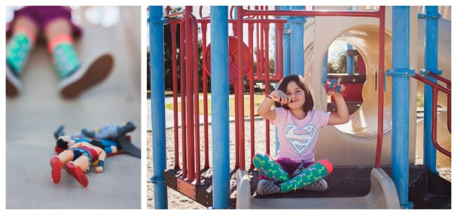 little girl playing with super hero action figures on a playground