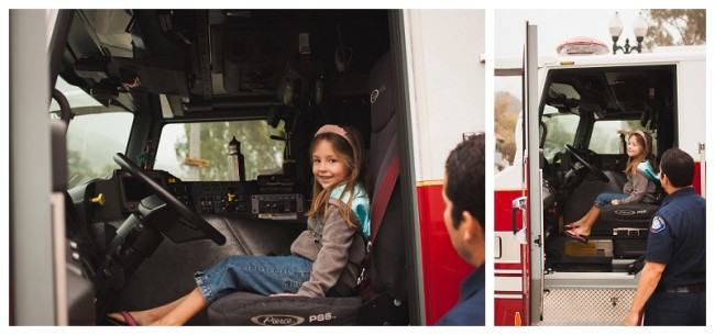 little girl sitting inside of a fire truck